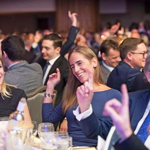Audience raising hand at event