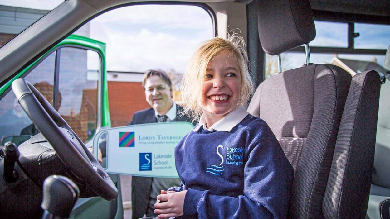 Child laughing behind the wheel of a minibus