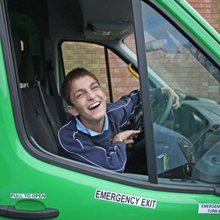 Little boy leaning out and laughing behind the wheel of a minibus