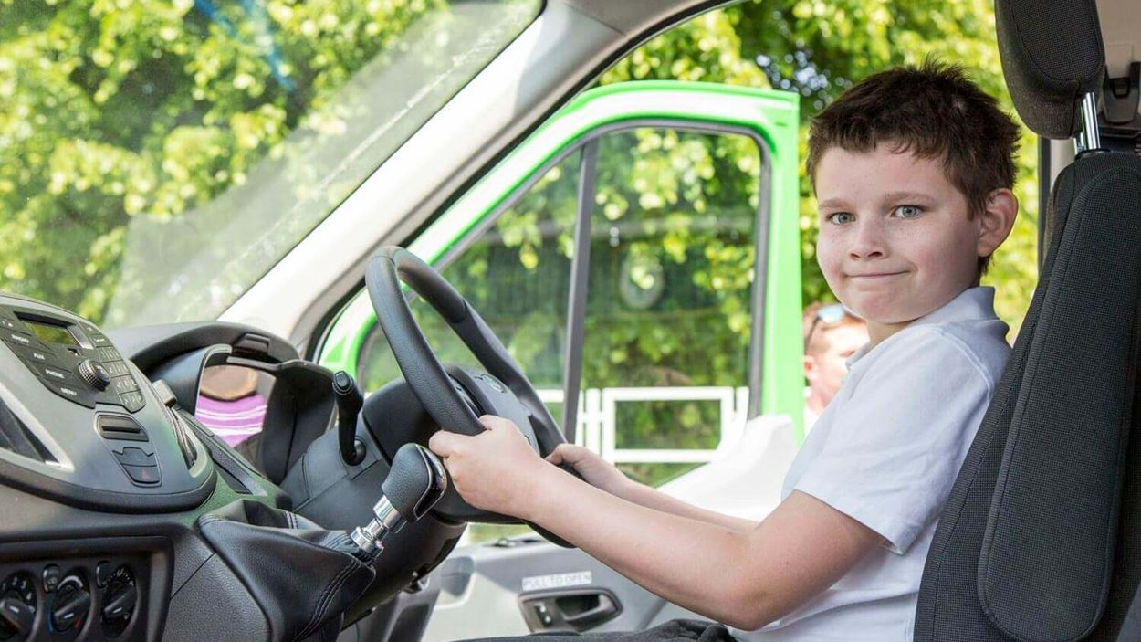 Little boy with both hands on the minibus wheel