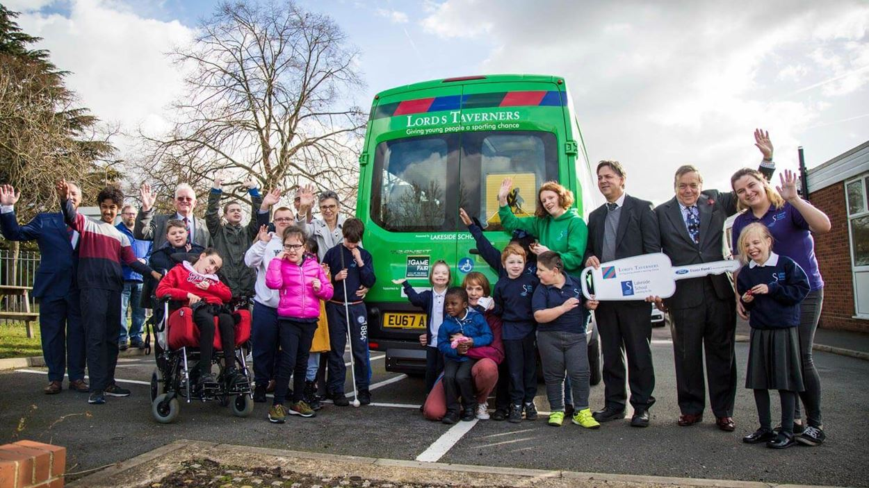 Group photo of all the children and stakholders posing infront of a green minibus