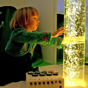 Little girl playing with a lava lamps