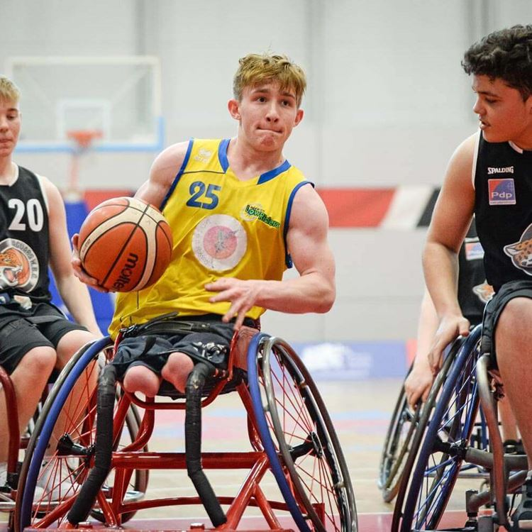 Action shot of a boy as he makes it down the court in the wheelchair basketball tournament
